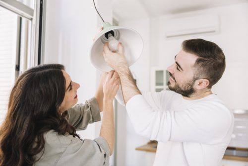 Pareja cambiando bombillas en su hogar: ahorrar para la remodelación de una casa.