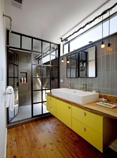 Cuarto de baño de estilo industrial con detalles en amarillo y madera.