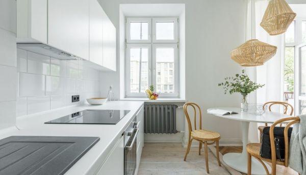 Una mesa redonda suaviza los volúmenes rectos de una cocina moderna.