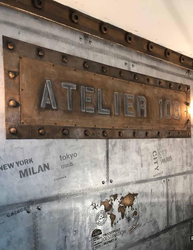 Atelier 103 avec enseigne style Eiffel et murs métal