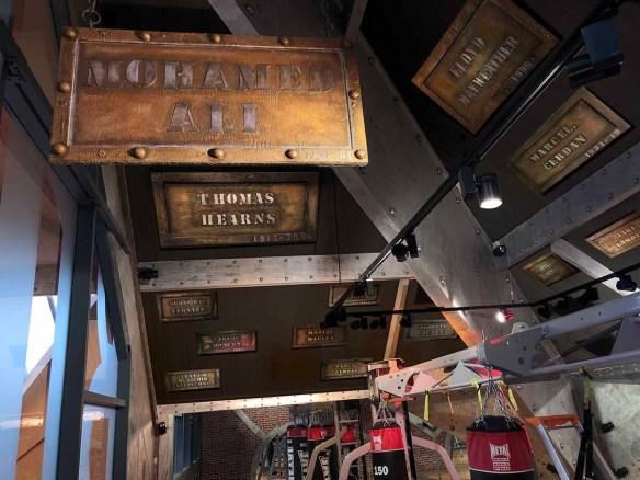 salle de boxe aux enseignes industrielles et boxeurs de légende