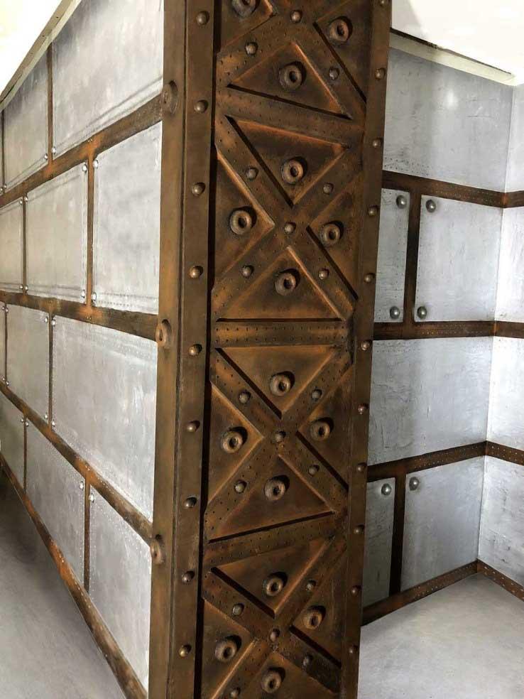 colonne style Eiffel sur murs métal à bandes oxydées