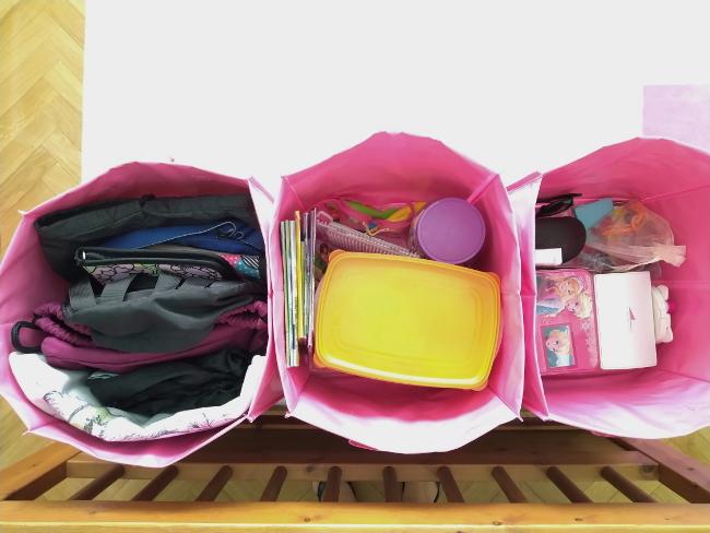Cajas con bolsos, juegos y complementos de mi hija adolescente.