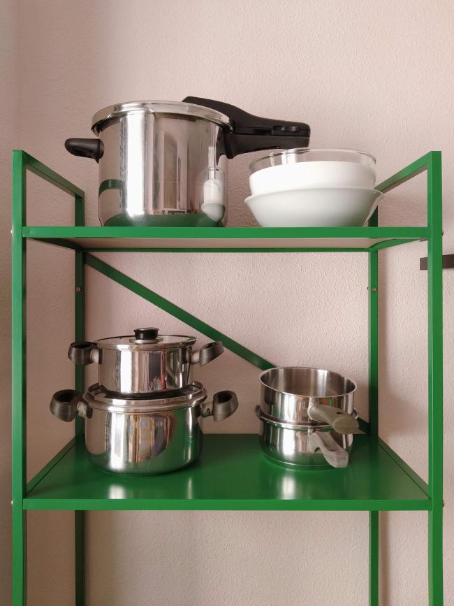 guardando ollas en baldas a la vista en la cocina