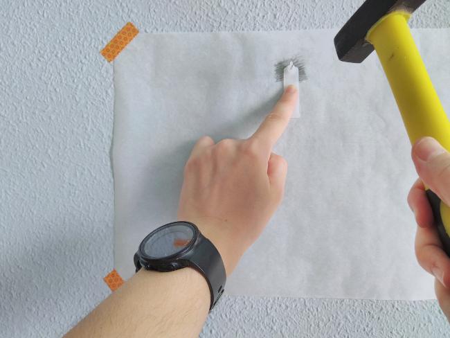 clavando con martillo un colgador para cuadros