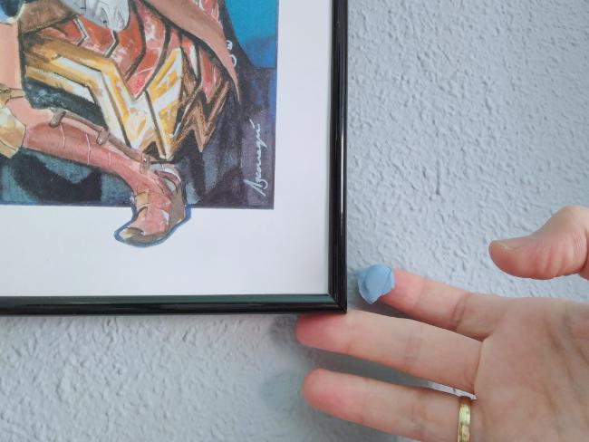 poniendo blu-tack en la esquina de un cuadro