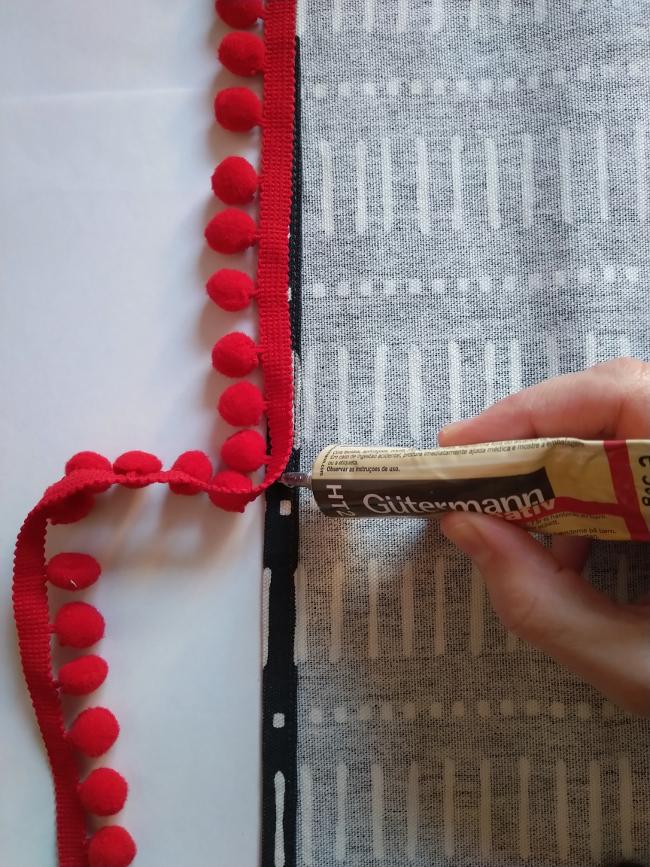 pegando la tira de pompones con pegamento textil