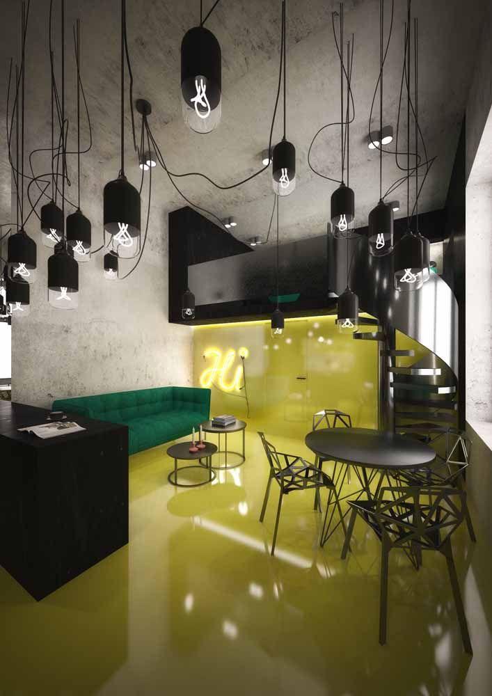 Uma combinação moderna e cheia de personalidade: amarelo no piso, preto na mobília e um ousado sofá verde para roubar a cena