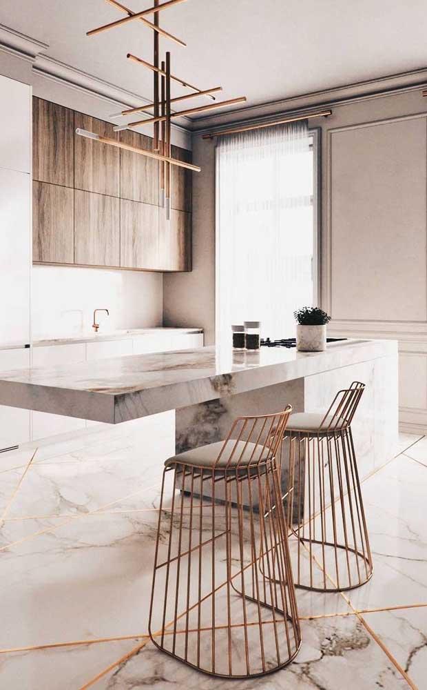 Cozinha moderna e sofisticada em tons de branco e marfim combinados ao tom metálico dourado das banquetas e da textura elegante do mármore