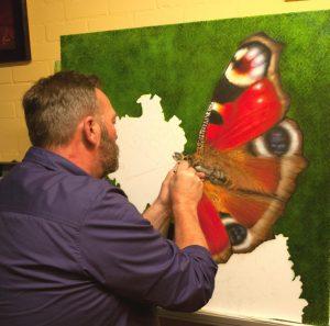 Anne Rozenberg aan het werk aan een airbrush schilderij