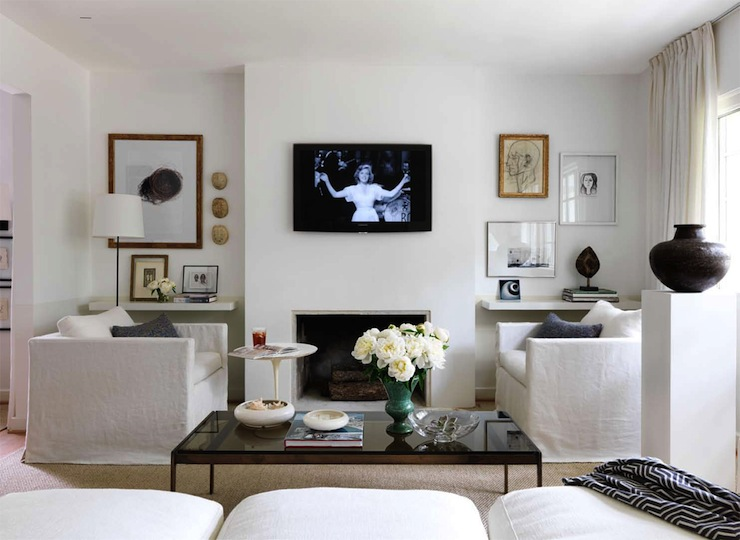 living rooms - white slipcovered sofas modern fireplace glossy black cocktail table eclectic art gallery sisal rug black vase TV over fireplace