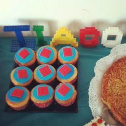 Pequenas peças de Lego vermelhas em cima dos cupcakes