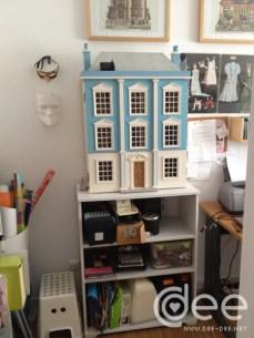 Casa de bonecas à entrada, com arrumação por baixo
