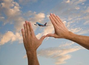 Man framing picture of airplane with his hands
