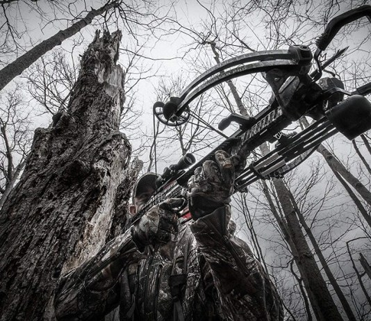 man in the woods with his top rated crossbow under 500 dollars