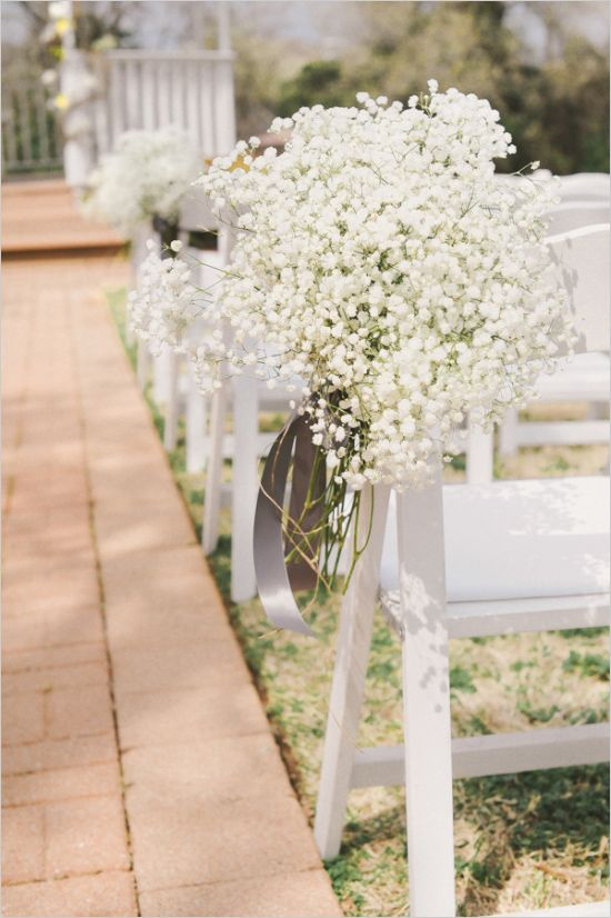 babys breath hanging from chairs at ceremony