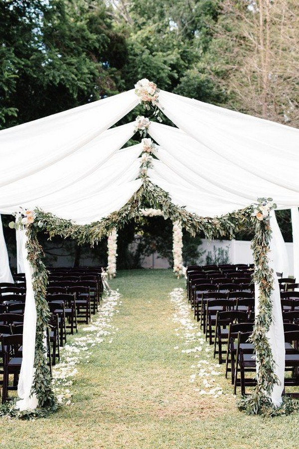 Outdoor wedding ceremony white fabric and greenery arches