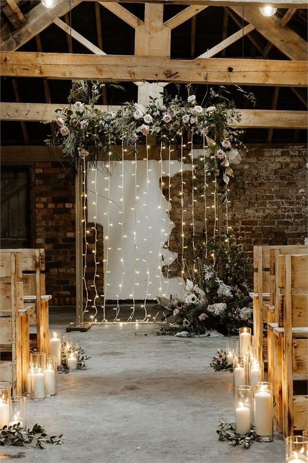 rustic wooden benches and floral fairy light backdrops, candle aisle decorations