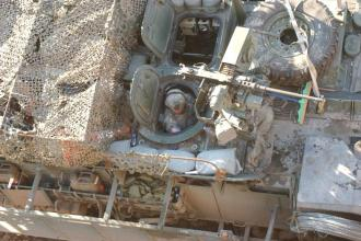 A U.S. Army gunner aboard a Stryker vehicle from 1st Battalion, 23rd Infantry Regiment, 2nd Infantry Division looks at his surroundings during a cordon and knock outside of Sadr City, Iraq, Dec. 26, 2006. A Stryker Product Improvement Program (S-PIP) is now underway. U.S. Army photo by Sgt. Tierney Nowland.