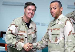Col. Lindsey Graham, a senior Senator from South Carolina, is presented a 386th Expeditionary Medical Group coin by Col. Andrew Montiero in the Contingency Air Medical Staging Facility on the Rock on April 9, 2009. U.S. Air Force photo by Tech. Sgt. Ian Carrier