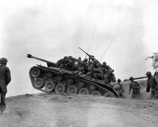 U.S. Army soldiers assigned to the 9th Infantry Regiment ride an M-26 Pershing tank as it moves forward to await an enemy attempt to cross the Naktong River, Sept. 3, 1950. U.S. Army photo by Cpl. Thomas Marotta