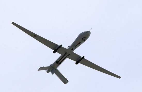 """A U.S. Air Force MQ-1 Predator unmanned aerial vehicle, armed with AGM-114 Hellfire missiles, performs a low altitude pass during the Aviation Nation 2005 air show at Nellis Air Force Base, Nev., on Nov. 13, 2005. UAVs can be used as """"pseudolites"""" to boost GPS signals during a given operation. U.S. Air Force photo by Airman 1st Class Jeffrey Hall."""