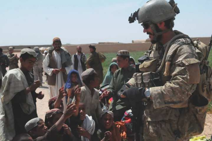 A United States Special Forces soldier hands out water drink mix to local Afghan children during a medical engagement in the Gereshk Valley, Helmand province April 15, 2010. Population-centric operations are a priority for CJSOTF-A. U.S. Army Photo by Sgt. Debra Richardson.