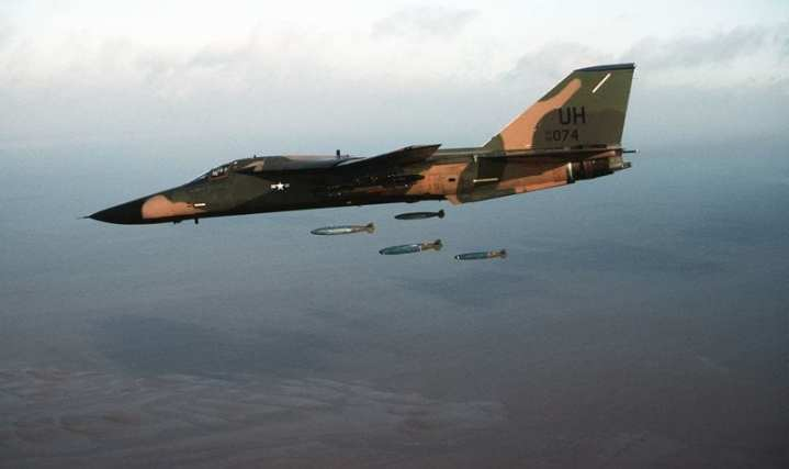 An F-111 aircraft of the 20th Tactical Fighter Wing, 3rd Air Force, RAF Upper Heyford, dropping bombs on a target range. DoD photo