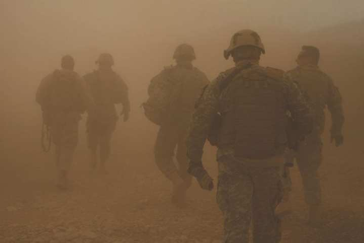 Soldiers and Marines walk through rotor wash from a UH-60 Black Hawk helicopter as they move toward a forward operating base in the village of Darrah-I-Bum, Badghis province, Afghanistan, Jan. 5, 2011. The cadre of personnel accompanied International Security Assistance Force Command Sgt. Maj. Marvin L. Hill on a visit to the Marines, sailors, and soldiers of Special Operations Task Force-West living and working in Darrah-I-Bum. U.S. Marine Corps photo by Sgt. Brian Kester