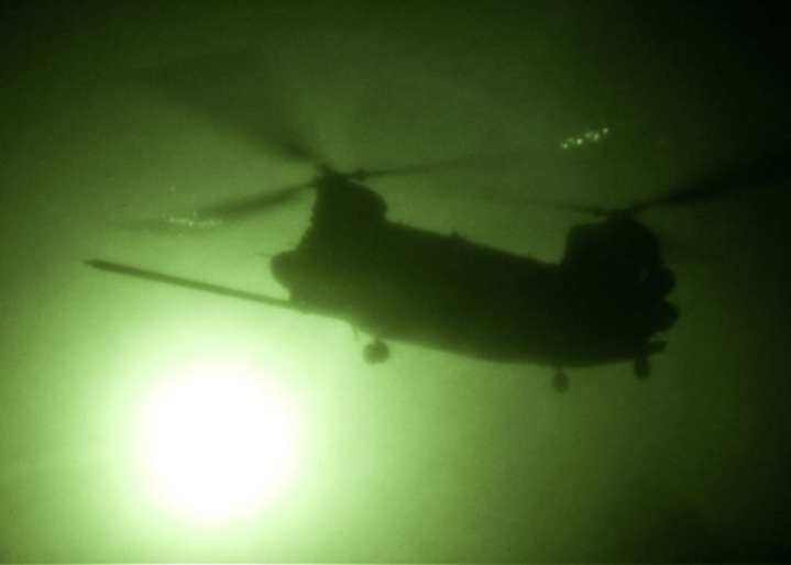An MH-47 Chinook seen during a night mission through night vision goggles