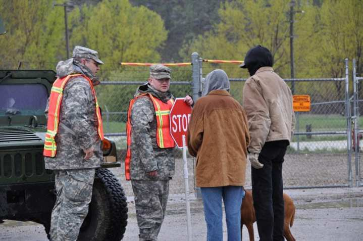 Montana Army National Guardsmen talk with residents about crossing into a washed out area in Roundup, Mont., May 31, 2011. Montana Gov. Brian Schweitzer sent National Guard troops to Roundup after heavy rains caused severe flooding in the area. DoD photo by Maj. Lori Hampa, U.S. Army