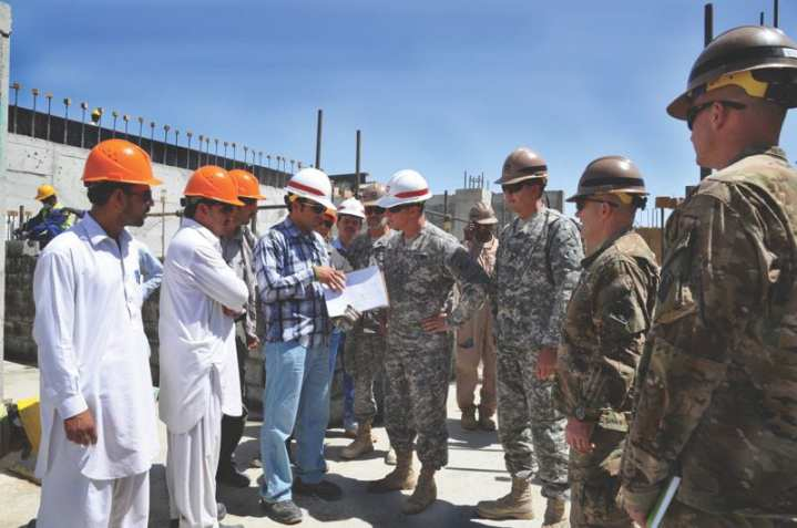 An Afghanistan quality assurance representative and Technologists, Inc., representatives (in orange hats) provide an overview of the Mazar-e-Sharif Area Office construction project at Camp Shaheen, Aug. 17, 2011, to (left to right) Transatlantic District Commander Maj. Gen. Kendall P. Cox, construction representative David Gaynor, Afghanistan Engineer District-North Commander Col. Christopher W. Martin, and Mazar-e-Sharif Area Office Officer-in-Charge Lt. Col. Brian S. Manus. Photo by Joseph Marek (AED-North)