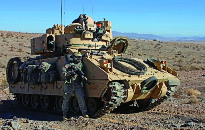 A U.S. Army soldier from the 3rd Armored Brigade Combat Team, 1st Infantry Division, pulls security next to a M2 Bradley Infantry Fighting Vehicle during Decisive Action rotation 13-03, Jan. 19, 2013, at the National Training Center in Fort Irwin, Calif. Decisive Action rotations are geared toward an adaptive enemy in a complex environment. U.S. Army photo by Sgt. Eric M. Garland II