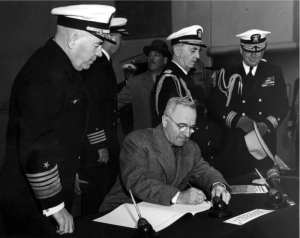 Seated at the same table upon which the instrument of surrender was signed in Tokyo Bay the previous month, President Harry S Truman signs the guest log on board the USS Missouri (BB 63) during a visit to the ship in 1945. Standing behind him, from left: Adm. Jonas H. Ingram, Commander in Chief of the Atlantic Fleet; Capt. Stuart S. Murray, skipper of the Missouri; Grover Whalen, chairman of the mayor's reception committee for the president; Adm. William Leahy, Chief of Staff to the President; New York City Mayor Fiorello LaGuardia (partially obscured); and Commodore James K. Vardaman, Jr., naval aide to the president. U.S. Navy photo