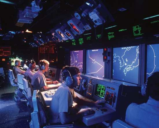 Crew members monitor radar screens in the combat information center aboard the guided missile cruiser USS Vincennes (CG 49), Jan. 1, 1988. U.S. Navy photo