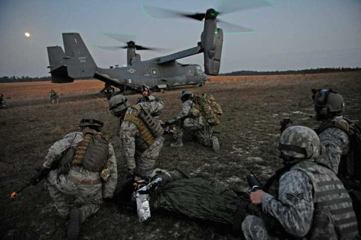U.S. Air Force airmen wait to load a simulated aircraft crash victim onto a CV-22 Osprey aircraft for the Emerald Warrior exercise March 7, 2012. The primary purpose of Emerald Warrior is to exercise special operations components in urban and irregular warfare settings to support combatant commanders in theater campaigns. Emerald Warrior leverages lessons learned from Operation Iraqi Freedom, Operation Enduring Freedom, and other historical lessons to provide better trained and ready forces to combatant commanders. U.S. Air Force photo by Tech Sgt. Charles Larkin Sr.