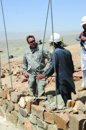 Hans Miller, project engineer at the Tarin Kowt resident office, discusses the perimeter wall construction at the Afghan National Police district headquarters construction site in Gaiti, Daykundi province, with Wahid, a USACE quality assurance representative, Sept. 12, 2011. U.S. Army Corps of Engineers photo by Karla Marshall