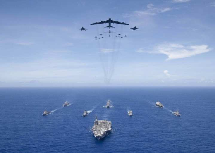 The aircraft carrier USS Ronald Reagan (CVN 76), foreground, leads a formation of Carrier Strike Group Five ships as Air Force B-52 Stratofortress aircraft and Navy F/A-18 Hornet aircraft pass overhead for a photo exercise during Valiant Shield 2018 in the Philippine Sea Sept. 17, 2018. (U.S. Navy photo by Mass Communication Specialist 3rd Class Erwin Miciano)