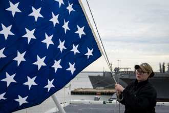 Quartermaster 2nd Class Taylor Miller, from Kent, Ohio, unfurls the union jack on the jack staff of the aircraft carrier USS Dwight D. Eisenhower (CVN 69). Dwight D. Eisenhower is undergoing a planned incremental availability during the maintenance phase of the Optimized Fleet Response Plan. (U.S. Navy photo by Mass Communication Specialist 3rd Class Kaleb Sarten/Released)