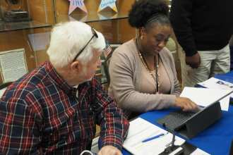 Army Veteran Larry Campbell gets updated on the spot by program support assistant Kendia Owens at the Columbia VA Health Care System Open House, Jan. 25. Campbell was one of several hundred who came through to get information and highlights.
