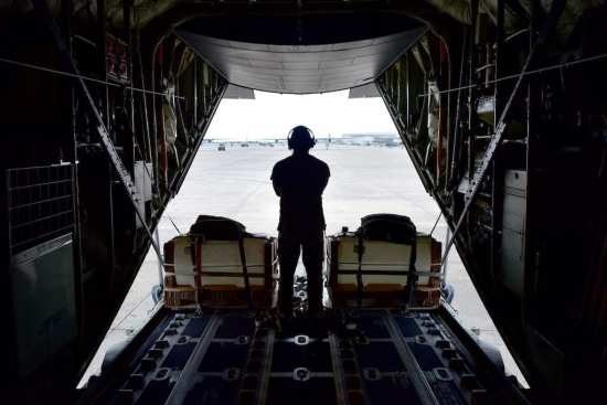 U.S. Air Force Tech Sgt. Luke Hughes, 61st Airlift Squadron instructor loadmaster noncommissioned officer in charge of training, looks out the back of a C-130J during the fly-in exercise at Little Rock Air Force Base, Arkansas, March 13, 2019. The second-annual fly-in includes C-130J units from around the globe. (U.S. Air Force photo by Airman 1st Class Kristine M. Gruwell)