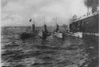 L-type submarines alongside USS Bushnell (Submarine Tender # 2) at Bantry Bay, Ireland, in 1918. These submarines are, from left to right: unidentified submarine; USS L-1 (Submarine # 40); USS L-10 (Submarine # 50); USS L-4 (Submarine # 43); and USS L-9 (Submarine # 49).