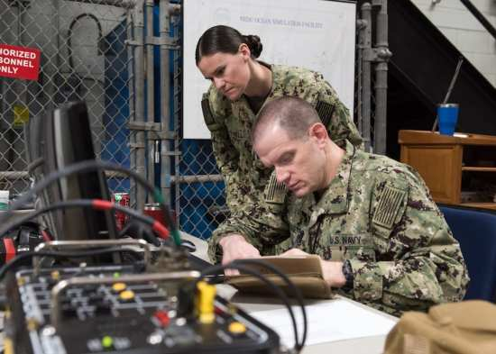 Research Psychologist Lt. Jenna Jewell and Research Physiologist Lt. Travis Doggett monitor aircrew vitals during flight patterns in the Fluctuating Altitude Simulation Technology (FAST) system Jan. 14, 2019 at Navy Experimental Diving Unit. The system was developed and built by Naval Surface Warfare Center Panama City Division. (U.S. Navy photo by Anthony Powers/Released)