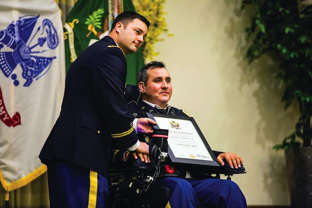 """Maj. Sean Hoey, left, pauses for a photo while holding Chief Warrant Officer Romulo """"Romy"""" Camargo's certificate of retirement Feb. 26. Camargo, paralyzed from the neck down by a gunshot sustained in 2008, retired to focus on his nonprofit organization, the Stay in Step Foundation, whose mission is to serve wounded warriors"""