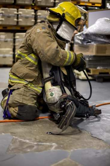 A firefighter loosens a strap on his pack during an air pack familiarization drill May 20, 2019 on United States Army Garrison Torii Station, Okinawa, Japan. The training was designed to familiarize the firefighters with their gear as well as enhance their abilities to perform during stressful situations. For many of the firefighters this was the first time receiving this kind of hands on training. (U.S. Marine Corps photo by Lance Cpl. Nicole Rogge)