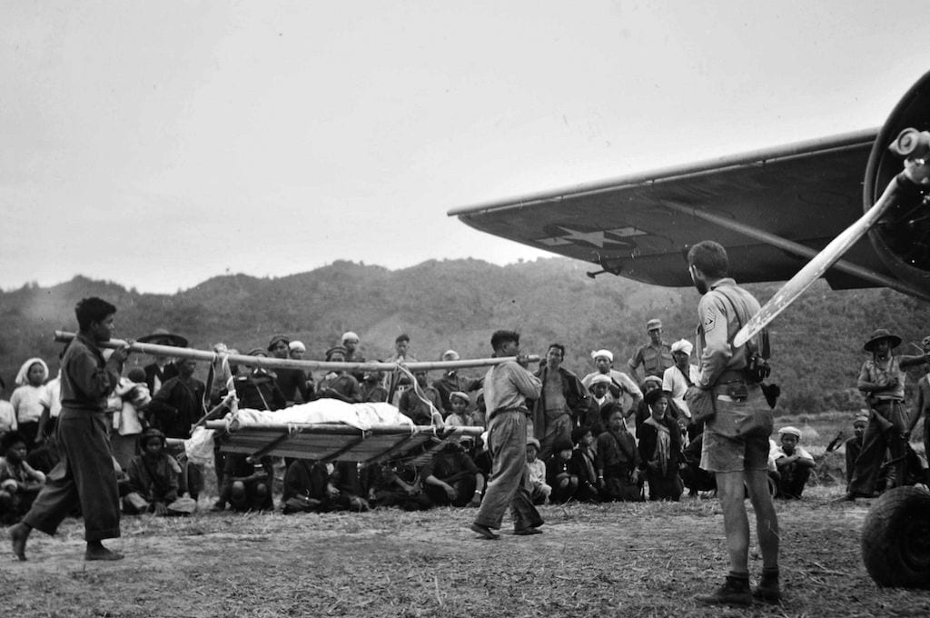 Air evacuation by light aircraft were a lifeline for the 5307th's casualties. Here, Kachins carry a casualty to a Stinson L-1 while its NCO pilot waits