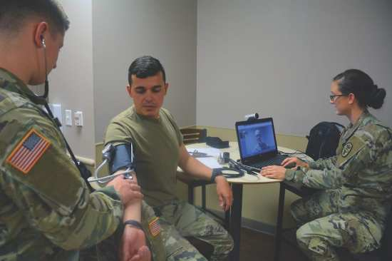 "Mobile medic Spc. Amanda Knight prepares for a video conference with a medical provider while mobile medic Spc. Joshua Rath checks Spc. Joao Dos Santos Faustino's vitals during an early morning ""sick call"" at the 232nd Medical Battalion, Sept. 25, 2017. A team of mobile medics used a combination of virtual and hands-on health care to triage the soldiers who reported to morning sick call. U.S. Air Force photo by Robert Shields"