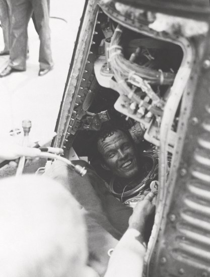 Astronaut L. Gordon Cooper, Jr., has a smile for the recovery crew of the USS Kearsarge after being brought on board from a successful 22-orbit mission in his Mercury spacecraft Faith 7. Cooper is still sitting in his capsule, with his helmet off.