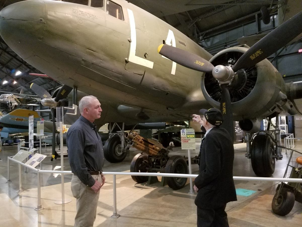 """Air Force Research Laboratory Aerospace Systems Directorate employee Kevin Price (left) and World War II veteran Jim """"Pee Wee"""" Martin look over the C-47 aircraft displayed at the National Museum of the United States Air Force on August 30, 2019. Price will accompany the 98-year-old Martin in September as he travels to the Netherlands to parachute into the region he helped liberate 75 years ago as part of Operation Market Garden. (U.S. Air Force Photo/Holly Jordan)"""