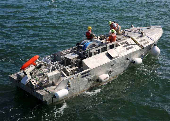 """A Sailor and civilian technicians monitor an unmanned surface vehicle (USV), after it was launched from Military Sealift Command's expeditionary sea base, USNS Hershel """"Woody"""" Williams (T-ESB 4), into the Chesapeake Bay, Sept. 14. The USV is a mine counter measure platform and the evolution was the first time a USV has been launched and recovered by a Military Sealift Command ship. (U.S. Navy photo by Bill Mesta/Released)"""